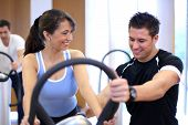 image of vibration plate  - Instructor in a gym explains a vibration plate to a woman