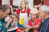 stock photo of patron  - Annoyed waitress and group of patrons arguing about the menu - JPG