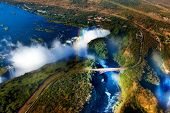 stock photo of southern  - Victoria Falls or Mosi-oa-Tunya is the widest waterfall in the world, located in southern Africa on the Zambezi River between the countries of Zambia and Zimbabwe.
