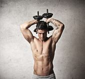 Muscular man raising behind his head two dumbbells