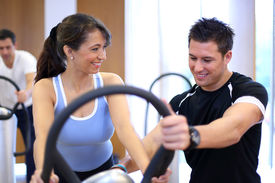 stock photo of vibration plate  - Instructor in a gym explains a vibration plate to a woman  - JPG