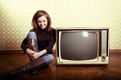 art portrait of young smiling ecstatic woman sitting near retro tv set in room with vintage wallpape