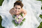 stock photo of bunch roses  - High View Portrait Of Beautiful Happy Bride Sitting On The Grass - JPG