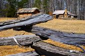 stock photo of log fence  - Wooden Log Fence Surrounding a Cabin in the Woods - JPG