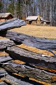 foto of log fence  - Wooden Log Fence Surrounding a Cabin in the Woods - JPG