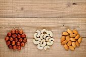 Hazelnuts, Almonds And Cashew Nuts On Wooden Background