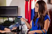 stock photo of cash register  - Cute young woman paying with a credit card in a cash register and smiling - JPG