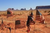 image of bute  - USA Monument Valley and American Flags flapping against a fence  - JPG