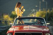 stock photo of muscle-car  - Young beautiful woman filming his boyfriend in a convertible car - JPG