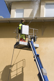 stock photo of pressure-wash  - A man working with a lift and pressure washer - JPG