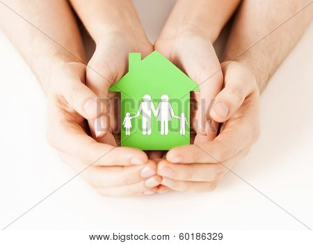 real estate and family home concept - closeup picture of male and female hands holding green paper h poster