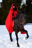stock photo of cloak  - beautiful woman with red cloak with horse outdoor in winter - JPG