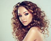 stock photo of perm  - A beautiful girl with long curly hair and fashion make - JPG