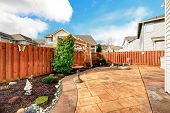 image of concrete  - Fenced backyard with concrete tile floor deck and decorated flower bed - JPG