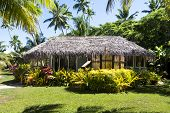 A traditional bure, or lodge, at a south pacific island resort surrounded by lush, green gardens.