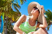 stock photo of panama hat  - Woman happy in a summer hat under the palm trees - JPG