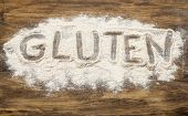 foto of allergy  - gluten word written  in wheat flour on wooden board - JPG