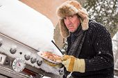 picture of sherpa  - Snow continues to fall on a middle aged man as he goes to light his barbeque only to find it covered in snow in the sub zero temperatures - JPG