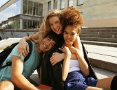 foto of school building  - cute group of teenages at the building of university with books huggings - JPG