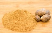 picture of ground nut  - Nutmeg seeds and ground nut meg on a bamboo chopping board - JPG