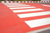 pic of zebra crossing  - white zebra crossing with red painted on asphalt street - JPG
