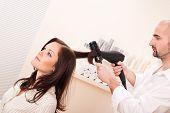 Постер, плакат: Профессиональный парикмахер с волосами сушилкой в салоне с клиентом