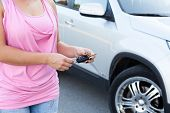 stock photo of pov  - Unrecognizable Caucasian woman with ignition key standing near own vehicle - JPG