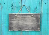 pic of blank  - Blank rustic sign hanging on weathered antique teal blue background - JPG