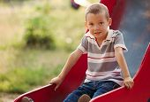 picture of playground  - Small boy playing on a slide in a kids playground sitting gripping the edges smiling shyly at the camera with copyspace - JPG