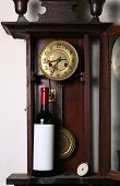 foto of pendulum clock  - Bottle of red wine with blank label template standing inside an old clock - JPG