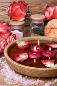 stock photo of unity candle  - Spa concept with roses pink salt and candles that float in a wooden bowl with water selective focus - JPG