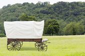 stock photo of covered wagon  - Covered wagon with white top in fields - JPG