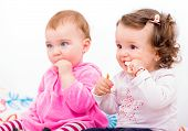 picture of teething baby  - Photo of two adorable baby sitting on the bed and nibbles - JPG