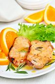 stock photo of pork cutlet  - Delicious pork cutlets with orange sauce on white plate - JPG