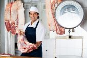 image of slaughterhouse  - Portrait of confident butcher holding raw meat in shop - JPG