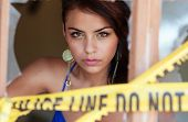 image of crime scene  - Pretty woman peering behind jagged broken glass window with crime scene tape - JPG