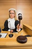 stock photo of court hammer  - Stern judge banging her hammer in the court room - JPG