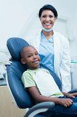 pic of dentist  - Portrait of female dentist examining boys teeth in the dentists chair - JPG