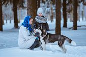image of puppies mother dog  - mother and young daughter playing with husky dog winter time - JPG
