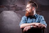 stock photo of adults only  - Profile of a handsome young bearded man looking away and sitting on chair - JPG