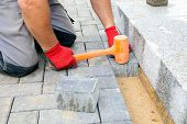 stock photo of paving stone  - Bricklayer places concrete paving stone blocks for building up a patio and a track in the backyard of a private house - JPG