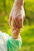 stock photo of stroll  - hand baby holds a finger mom love stroll - JPG