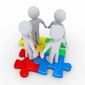stock photo of joining  - Four 3d people join on different colored puzzle pieces - JPG