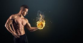 stock photo of combustion  - Handsome power athletic man bodybuilder doing exercises with dumbbell - JPG