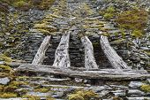 stock photo of gravity  - Only remaining wood bridge of gravity incline Cwm Penmachno Slate Quarry Snowdonia Wales United Kingdom - JPG
