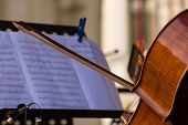 image of cello  - Cello with music symphony notes on black support on the scene - JPG