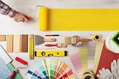 pic of interior decorator  - Decorator holding a painting roller and painting a wooden surface work tools and swatches at bottom banner with copy space - JPG