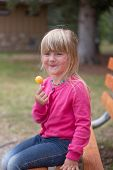picture of lolli  - Little girl having lolly pop at a park - JPG