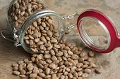 image of pinto bean  - Pinto beans spilling from a glass jar on a tile counter top - JPG