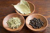 stock photo of bay leaf  - Dry herb served in wooden plate rosemary bay leaf black pepper - JPG